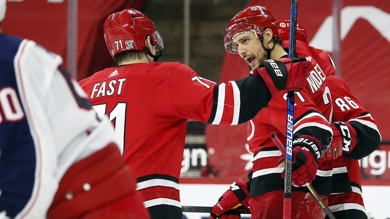 Carolina Hurricanes' Nino Niederreiter (21) celebrates his goal with teammate Teuvo Teravainen (86) and Jesper Fast (71) during the second period of an NHL hockey game against the Columbus Blue Jackets in Raleigh, N.C., Monday, Feb. 15, 2021. (AP Photo/Karl B DeBlaker)