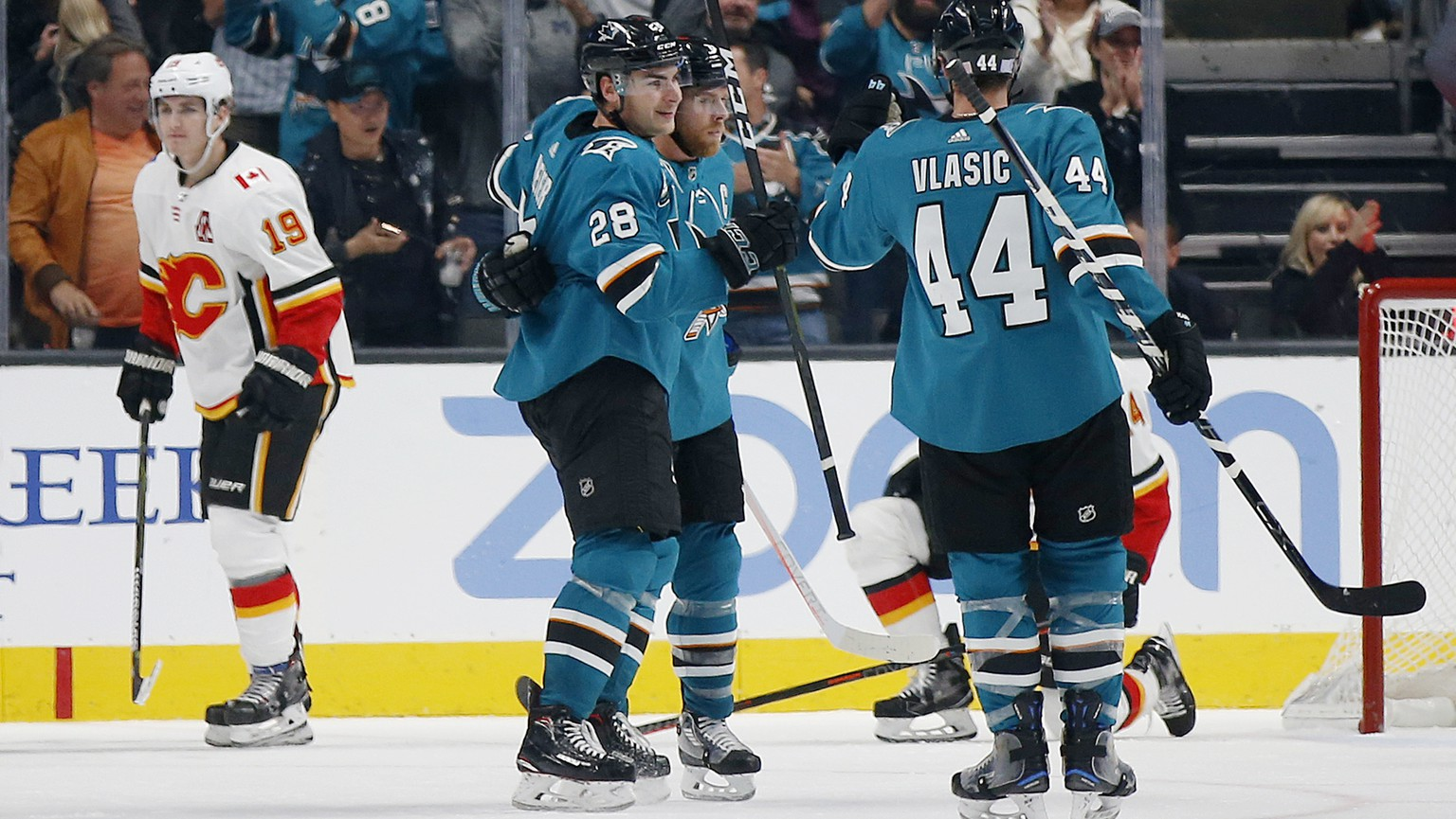 Calgary Flames' Matthew Tkachuk (19) skates away as the San Jose Sharks' Timo Meier (28), Joe Pavelski (8), center, and Marc-Edouard Vlasic (44) celebrate a goal in the third period of an NHL hockey game in San Jose, Calif., Sunday, Nov. 11, 2018. The Sharks won, 3-1. (AP Photo/Josie Lepe)