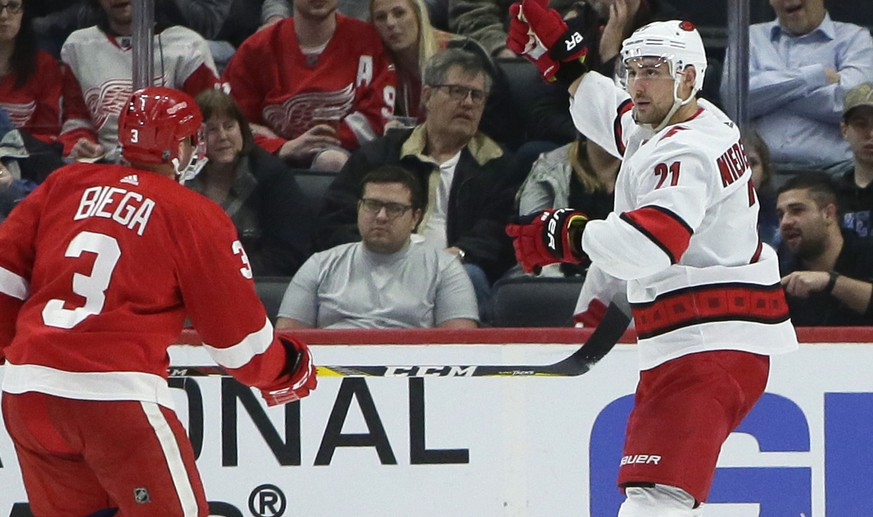 Carolina Hurricanes right wing Nino Niederreiter (21) celebrates his second-period goal in front of Detroit Red Wings defenseman Alex Biega (3) during an NHL hockey game Tuesday, March 10, 2020, in Detroit. (AP Photo/Duane Burleson)