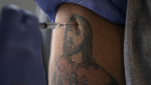 Farm worker Jorge Americano receives the Pfizer-BioNTech COVID-19 vaccine in his arm bearing a tattoo depicting Jesus at Tudor Ranch in Mecca, Calif., Thursday, Jan. 21, 2021. (AP Photo/Jae C. Hong)