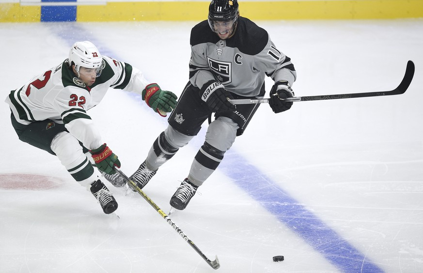 Minnesota Wild left wing Kevin Fiala, left, lunges to poke the puck away from Los Angeles Kings center Anze Kopitar during the first period of an NHL hockey game in Los Angeles, Saturday, Jan. 16, 2021. (AP Photo/Kelvin Kuo)
