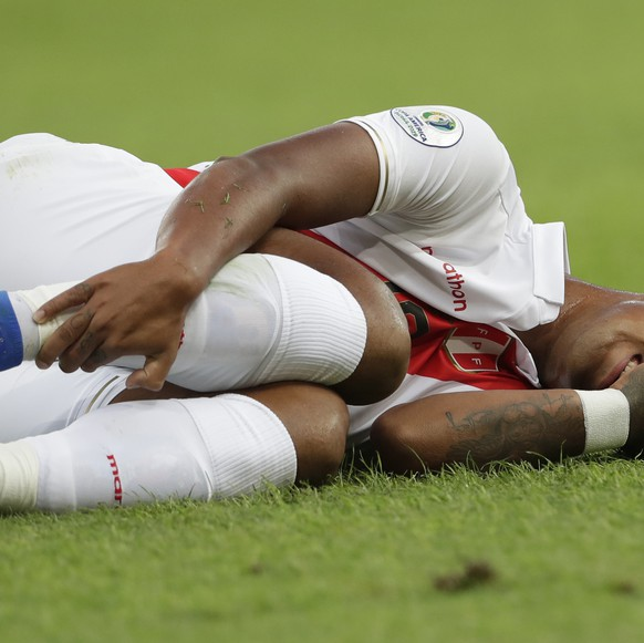 Peru's Yoshimar Yotun grimaces in pain after a rough play during the final match of the Copa America against Brazil at Maracana stadium in Rio de Janeiro, Brazil, Sunday, July 7, 2019. (AP Photo/Silvia Izquierdo)