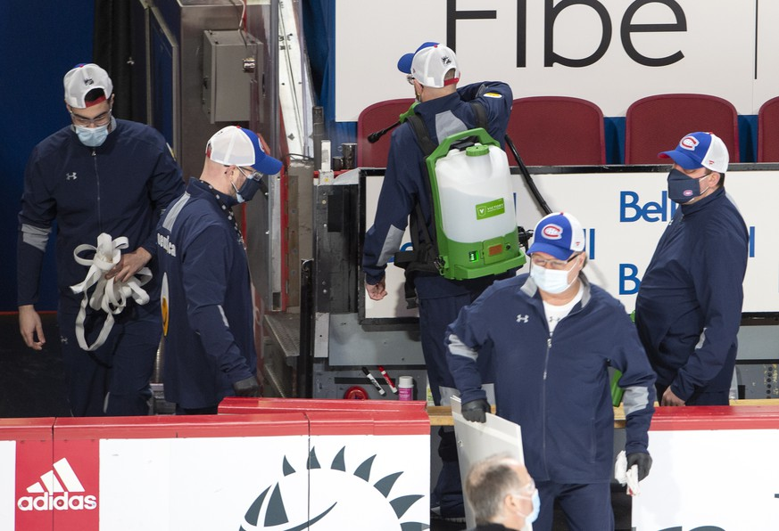 Arena workers clean the players' bench before NHL hockey action between the Edmonton Oilers and the Montreal Canadiens, in Montreal, Thursday, Feb. 11, 2021. The game had been delayed by an hour after an Oilers player was placed on the league's COVID-19 protocol. (Ryan Remiorz/The Canadian Press via AP)