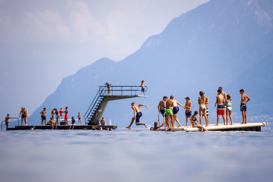 epaselect epa06909933 People enjoy the sunny and warm summer weather on a diving platform on the shore of Lake Geneva, in Lutry, Switzerland, 25 July 2018. Temperatures of up to 35 degrees Celsius currently dominate wide parts of Europe with only a few rainfalls here and there expected over the upcoming weekend, meteorologists predict.  EPA/VALENTIN FLAURAUD