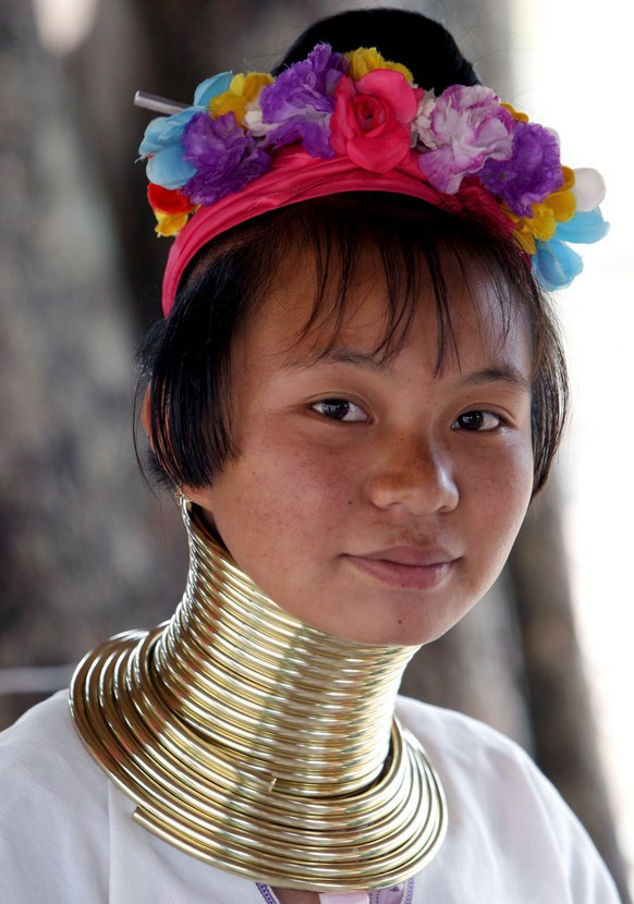 epa01288303 Marie, a Padung 'long neck' Karen woman, at her stall in a refugee tourist camp near Mae Tang, about 60km north of Chiang Mai, northern Thailand, 09 March 2008. She wears multiple brass rings around her neck which Padung 'long neck' or 'giraffe' women and girls are known for, a practise which pushes the collar bone down and compresses the rib cage, making the neck look longer. The handicraft camps have caused controversy, as has the plight of the Padung in Thailand as stateless people. Some say the wearing of the coils is only perpetuated for the tourist market, and that they are exploited. Some women have been denied refugee status when accepted by third countries. The women in this camp spoke of a better life in Thailand selling their handicrafts with a reliable income, when compared to their former situation in Burma.  EPA/BARBARA WALTON