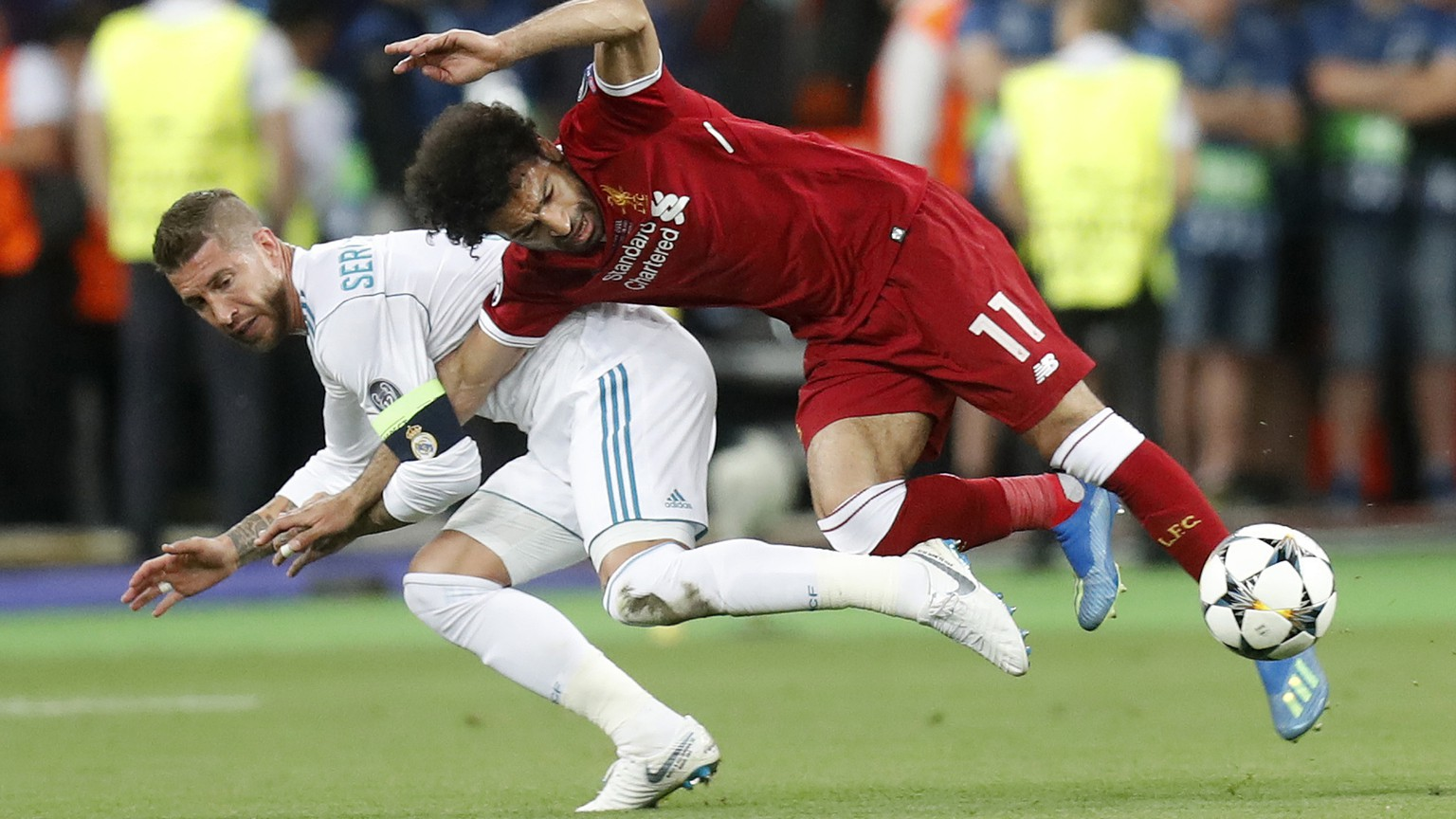 FILE - In this Saturday, May 26, 2018 file photo Real Madrid's Sergio Ramos, left, fouls Liverpool's Mohamed Salah during the Champions League Final soccer match between Real Madrid and Liverpool at the Olimpiyskiy Stadium in Kiev, Ukraine. Sergio Ramos isn't taking blame for the challenge that ended hurting Egypt star Mohamed Salah in the Champions League final. Salah left the field in tears after injuring his left shoulder in a tussle with Ramos with the score 0-0 in the first half. (AP Photo/Efrem Lukatsky, File)