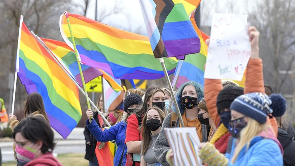 People wave pride flags and hold signs during a rally in support of LGBTQ students at Ridgeline High School, Wednesday, April 14, 2021, in Millville, Utah. Students and school district officials in Utah are outraged after a high school student ripped down a pride flag to the cheers of other students during diversity week. A rally was held the following day in response to show support for the LGBTQ community. (Eli Lucero/The Herald Journal via AP)