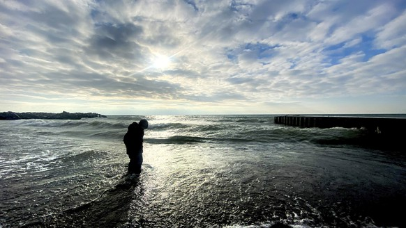 A young boy plays in the surf by the shore of Lake Ontario in Toronto on Thursday, Jan. 21, 2021. (Frank Gunn/The Canadian Press via AP)