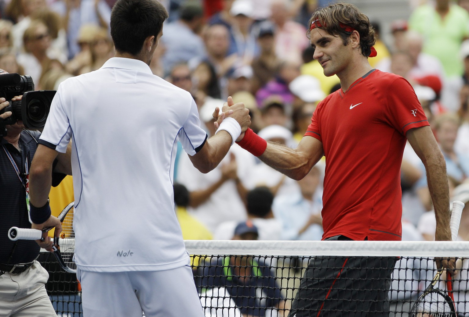 Roger Federer of Switzerland, right, shakes hands with Novak Djokovic of Serbia after losing a semifinal match at the U.S. Open tennis tournament in New York, Saturday, Sept. 10, 2011. (AP Photo/Matt Slocum)